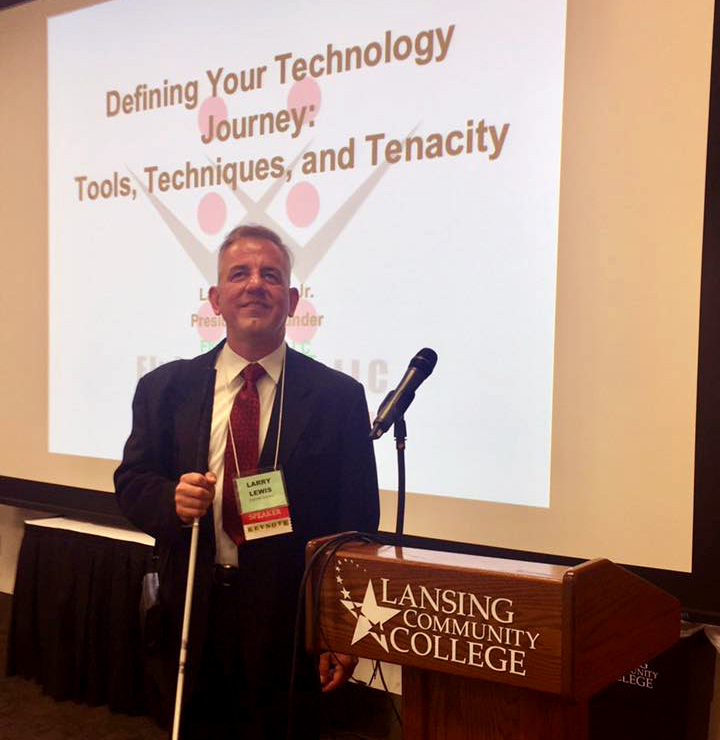 Flying Blind, LLC's Founder, Larry Lewis, in suit and tie, stands smiling in front of a large, wall-sized projection of the Flying Blind, LLC Logo, upon which are the words, 'Defining Your Technology Journey: Tools, Techniques, and Tenacity'. To Larry's left is a podium emblazoned with the logo for Lansing Community College.