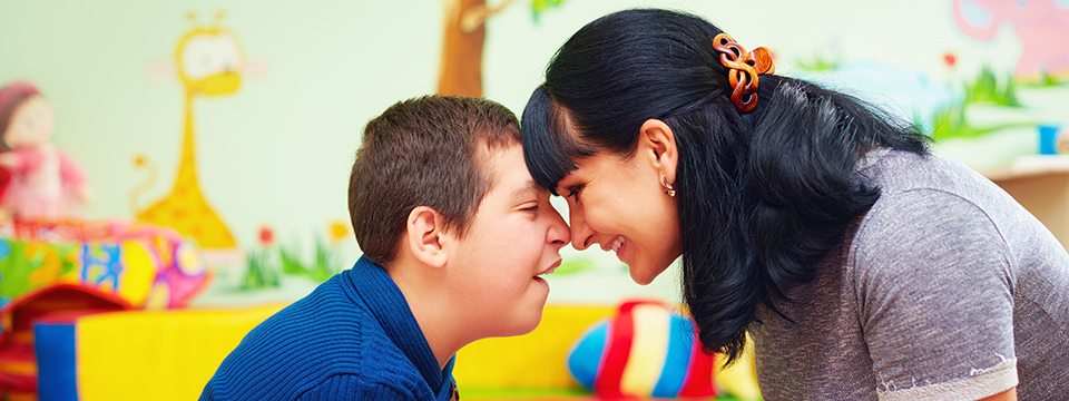 A soulful moment. Forehead to forehead. Portrait of a mother and her beloved son with disability at a rehabilitation center.