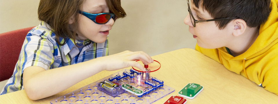 Two students get hands-on with the colorful circuit board of Snap Circuits Jr.