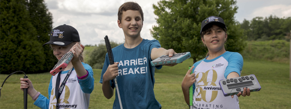 Three young Braille Challenge participants are smiling and enjoying the outdoors, each holding their cane and each holding a Chameleon 20.