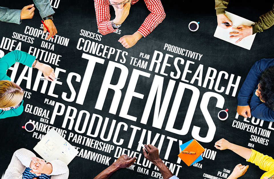 Eight people of varying backgrounds sit together for a meeting at a table with large words printed on it. These words include trends, team, research, partnership and many others.