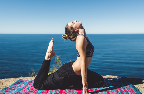 Beautiful photo of a woman, in yoga pose, on a blanket, on a mountain top, in front of the ocean.