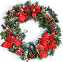 Photo of a beautiful circular wreath decorated with pine cones, pine tree fronds, and red poinsettas. The entire wreath is coated with a slight dusting of snow.